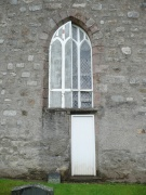 Partially blocked nave window with doorway into presbytery, from north-west
