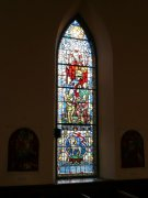A stained glass window depicting Christ with children